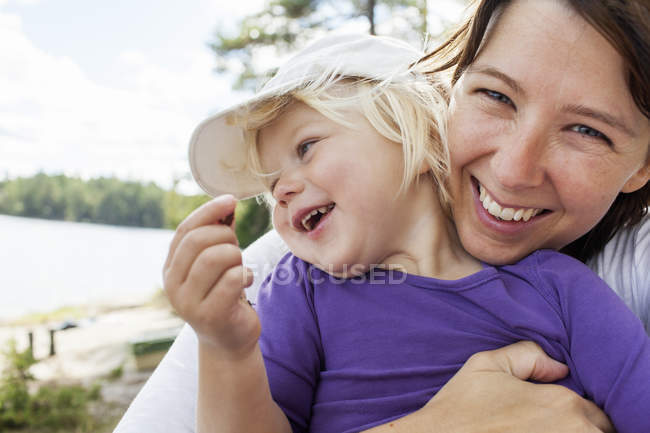 Mother holding daughter and looking at camera, focus on foreground — Stock Photo