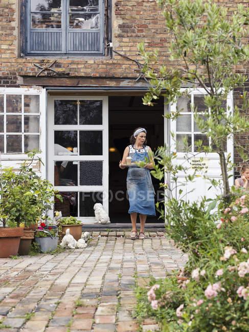 Mujer sosteniendo bandeja con comida caminando fuera de casa - foto de stock