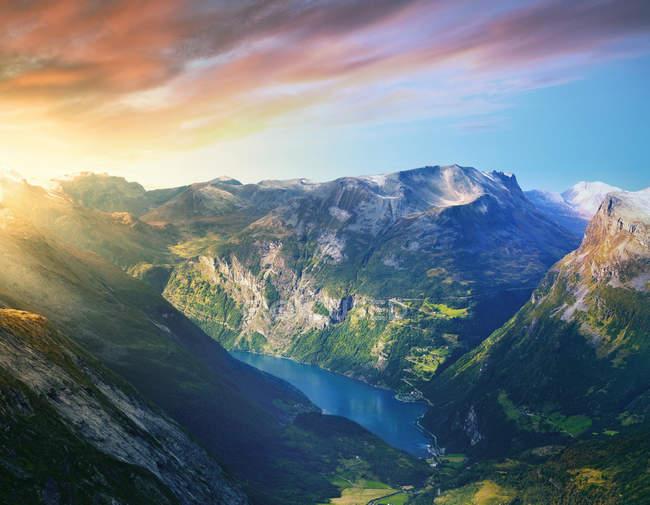 Фіорд з зеленим скель під хмарного неба захід сонця — стокове фото