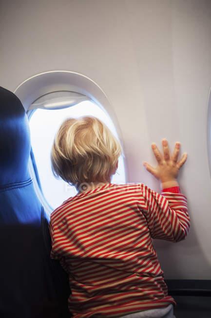 Visão traseira da menina olhando através da janela plana — Fotografia de Stock