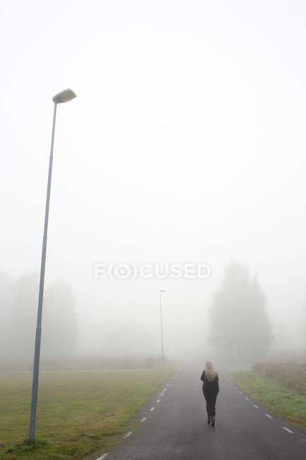 Donna che cammina lungo la strada nella nebbia — Foto stock