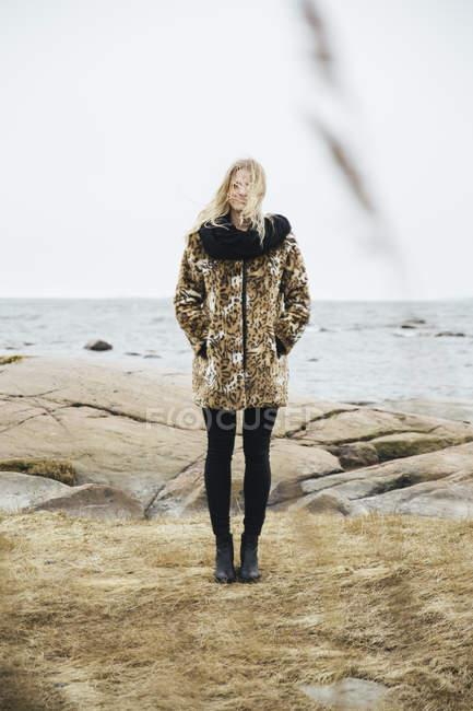 Giovane donna bionda in piedi al mare — Foto stock