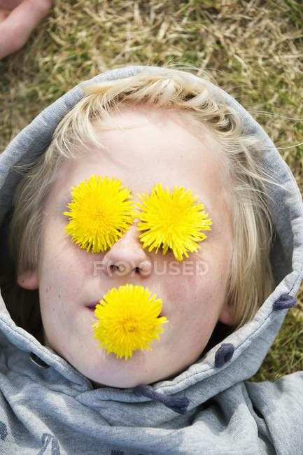 Вид мальчика с цветами на глазах и во рту — стоковое фото