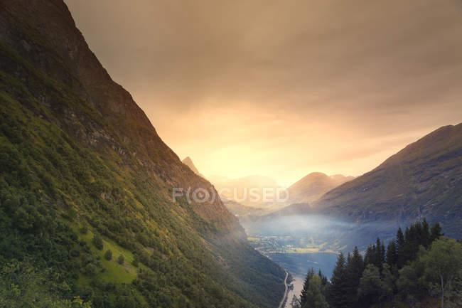 Elevata vista della nebbiosa valle montuosa al tramonto — Foto stock