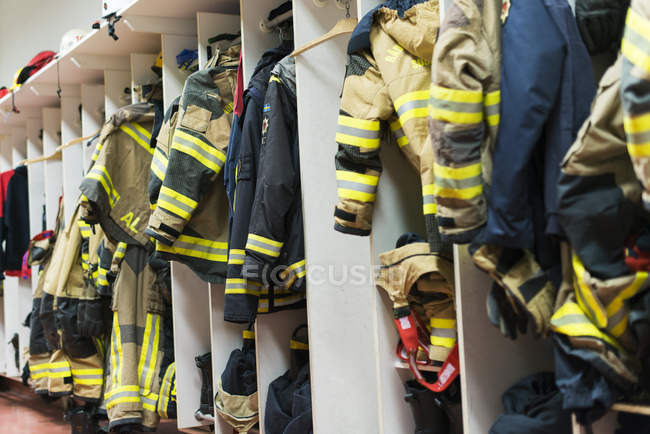 Fire station changing cubicles with firefighters uniform — Stock Photo