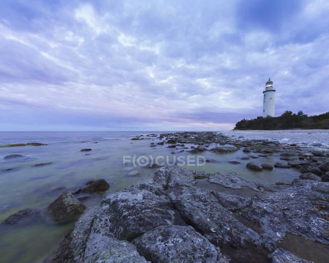 Tir longue exposition du phare au bord de mer rocheuse — Photo de stock