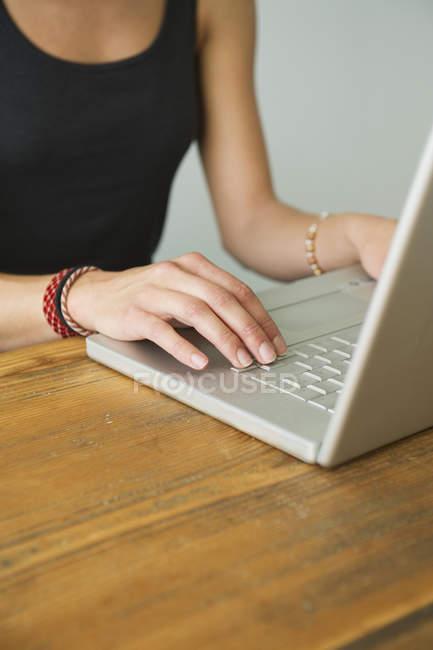 Cropped shot of woman using laptop — Stock Photo
