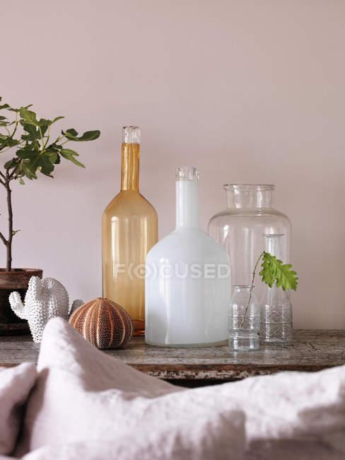 Botellas y jarrones vacíos en la mesa - foto de stock