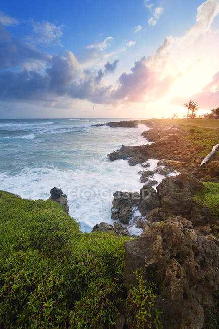 Rocky coastline under cloudy sunrise sky — Stock Photo