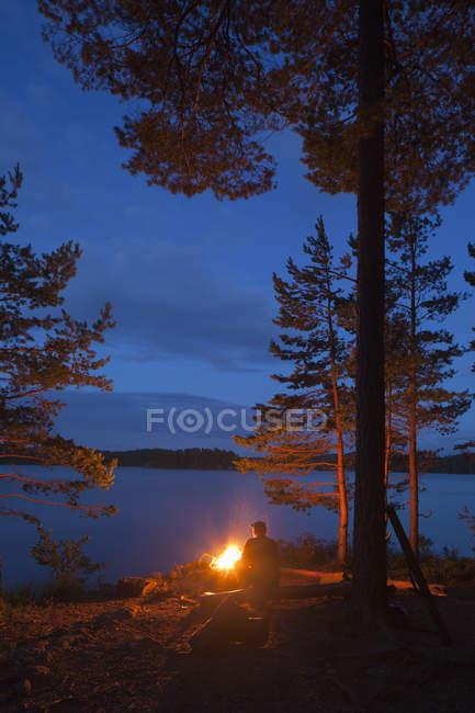 Vue arrière de l'homme par le feu de joie sur la rive — Photo de stock