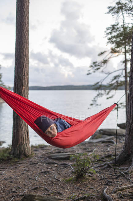 Boy lying in hammock by lake at sunset — Stock Photo