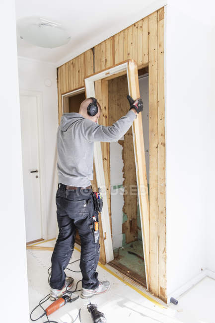 Rear view of young man renovating house — Stock Photo