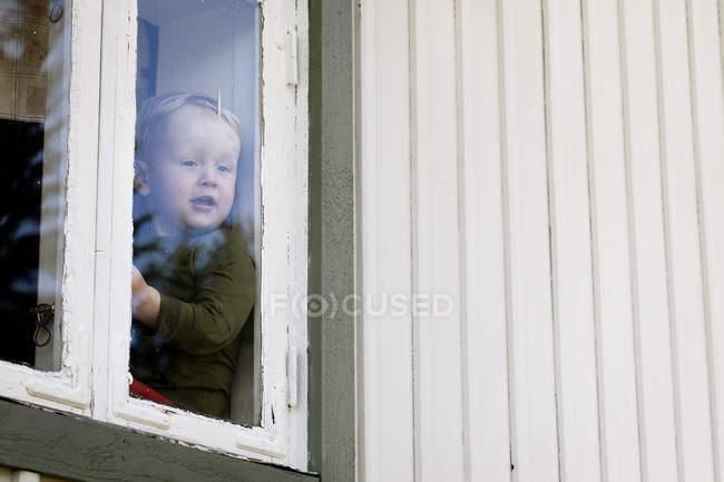 Vorderansicht des jungen Blick durch Fenster — Stockfoto
