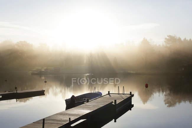 Дерев'яні jetty з причалюють човен у sunlight — стокове фото