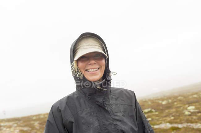 Посміхаючись жінці носити плащ і дивлячись на камеру — стокове фото