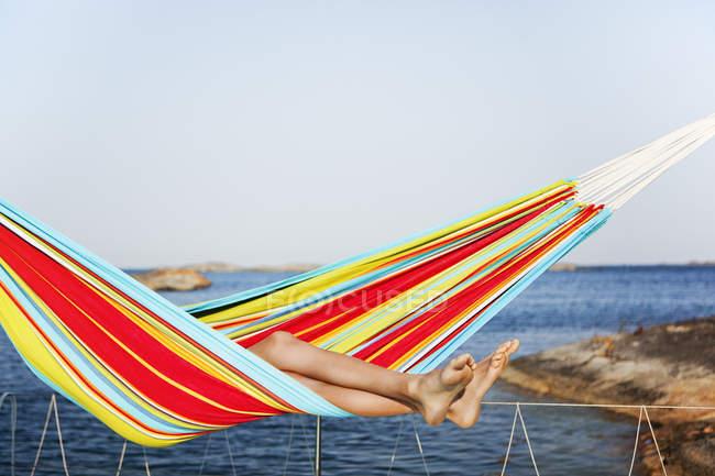 Мальчик-подросток лежит в гамаке у моря — стоковое фото