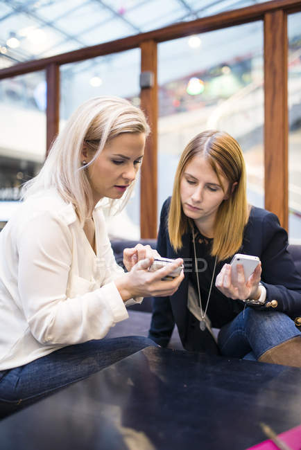 Two businesswomen looking at smartphones in office — Stock Photo