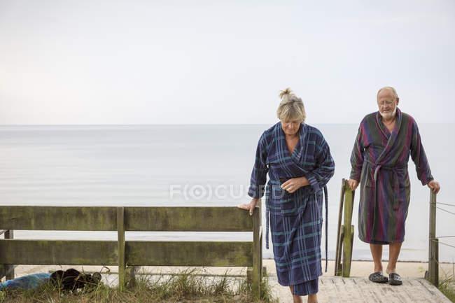 Pareja mayor que regresa de la playa en albornoces - foto de stock
