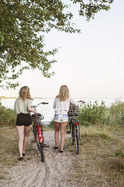 Vista traseira das duas adolescentes andando com bicicletas — Fotografia de Stock