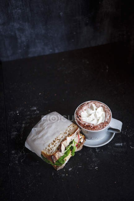 Cup of hot chocolate and sandwich on table — Stock Photo