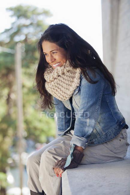 Женщина, сидящая на каменной скамейке с defocussed фоном — стоковое фото