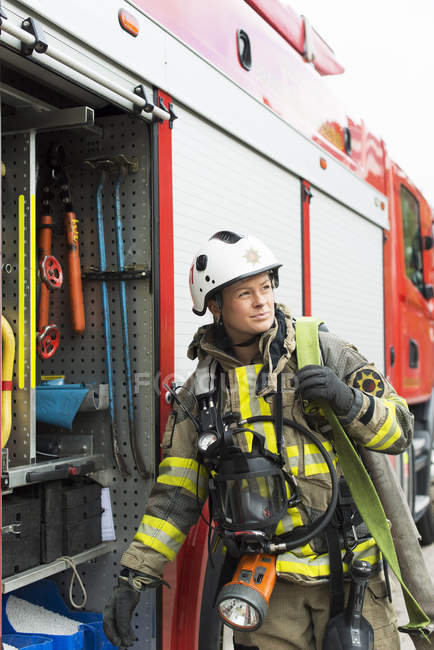 Жіночий пожежний з обладнанням, що стояв поруч, щоб пожежний автомобіль — стокове фото