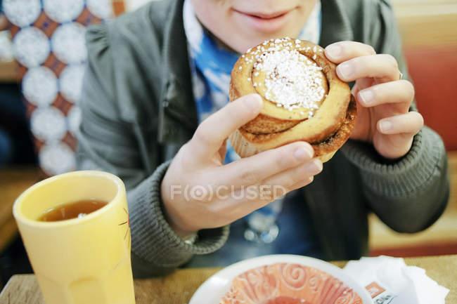Mujer joven comiendo bollo de canela - foto de stock