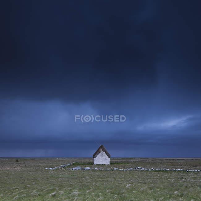 Casa solitária no campo sob o céu de tempestade — Fotografia de Stock