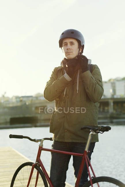 Portrait of man tying helmet strap, focus on foreground — Stock Photo