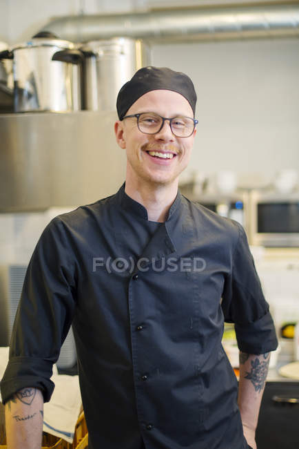 Front view of man looking at camera in cafe kitchen — Stock Photo