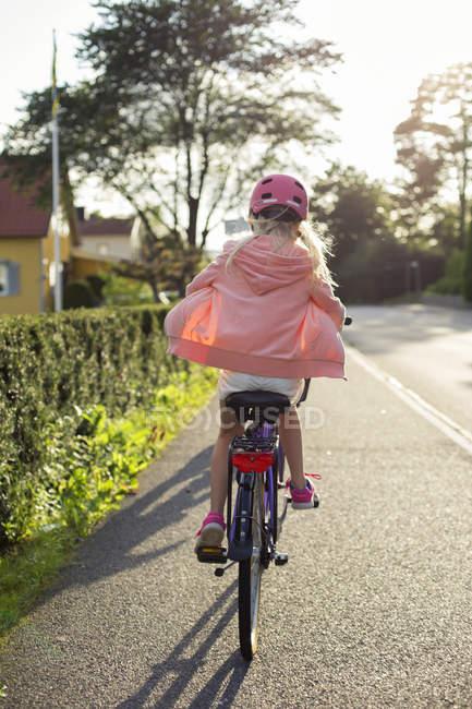 Fille portant un casque rose vélo d'équitation le long de la rue — Photo de stock