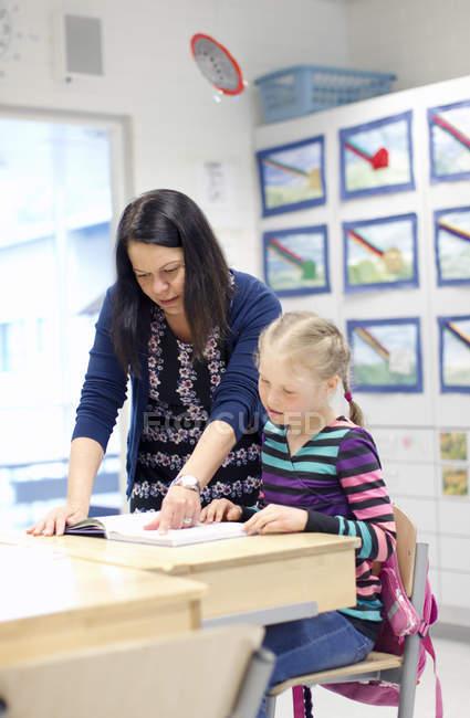 Mädchen mit Lehrer Lesebuch im Klassenzimmer, Fokus auf Vordergrund — Stockfoto