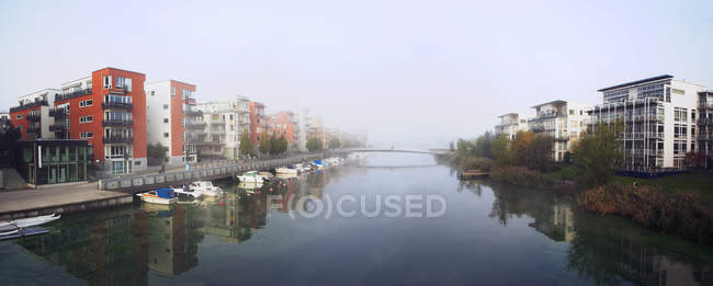 Panoramic view of buildings on riverbanks and moored boats — Stock Photo