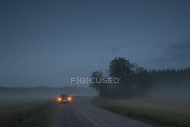 Car on foggy rural road at dusk — Stock Photo