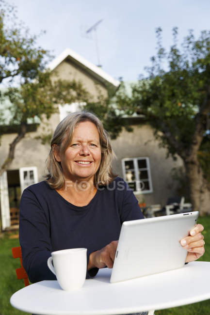 Mature woman using digital tablet at table in backyard — Stock Photo