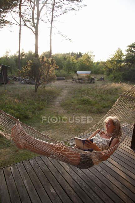 Senior woman reading book in hammock — Stock Photo