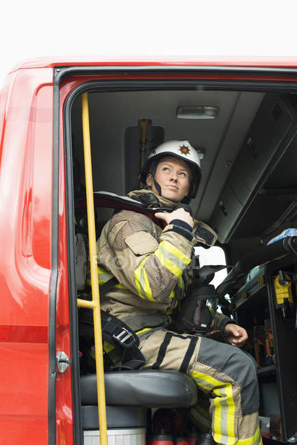 Female firefighter sitting in fire engine and looking up — Stock Photo