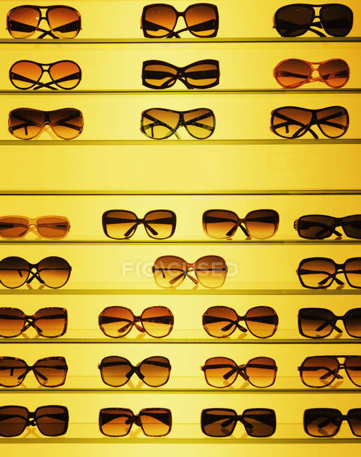 Stylish sunglasses on shelf in optics store — Stock Photo