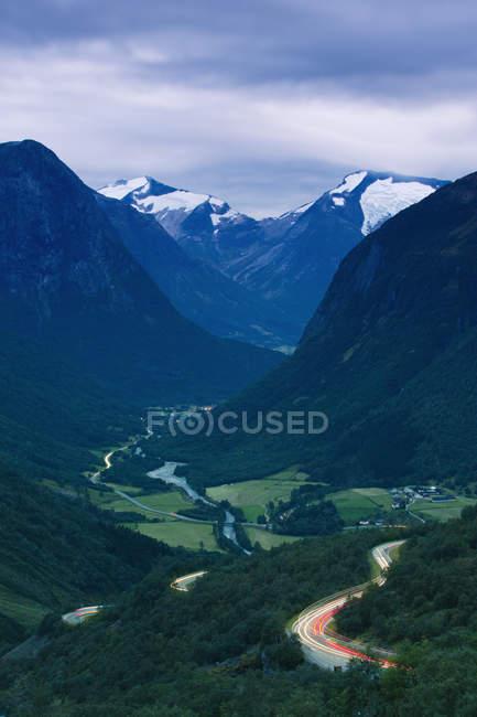 Tir longue exposition des montagnes, vallée verdoyante et sentiers de lumière de voiture sur route — Photo de stock