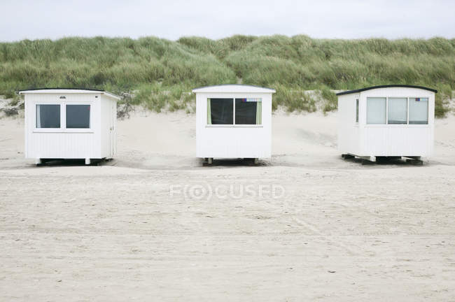Фронтальний вид білі хати на піщаному пляжі — стокове фото