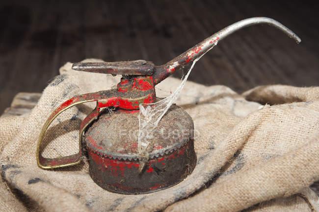 Envase de aceite oxidado en saco viejo - foto de stock
