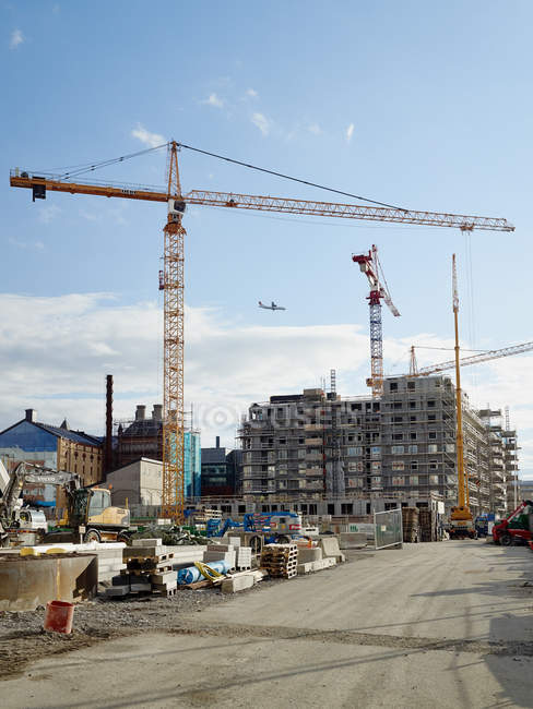 Unfinished building with construction cranes under blue sky — Stock Photo