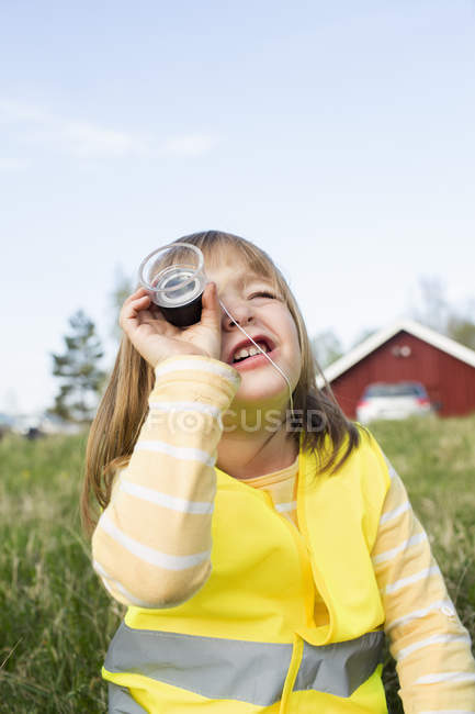 Girl looking through an magnifying glass, focus on foreground — Stock Photo