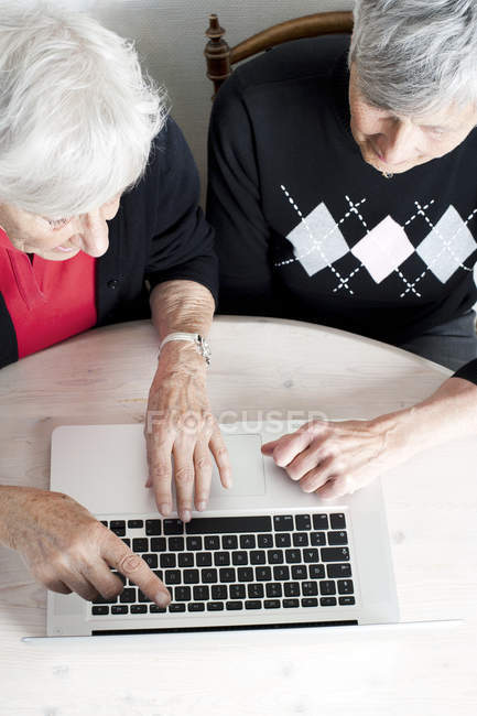 Overhead view of two senior women using laptop — Stock Photo