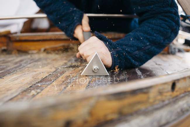 Man renovating wooden boat surface with tool — Stock Photo