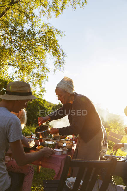 Family with small child having dinner in backyard at sunset — Foto stock