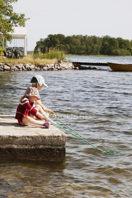 Vista laterale delle ragazze pesca nel lago, messa a fuoco su primo piano — Foto stock