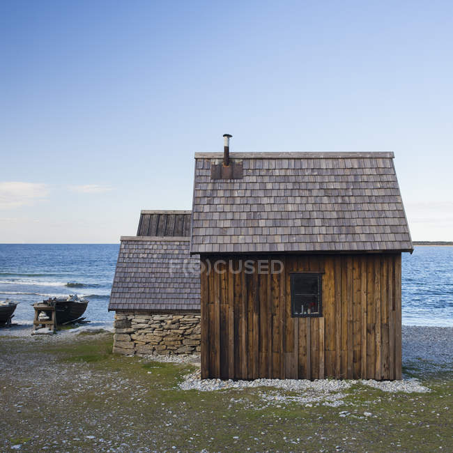Small wooden house on seashore under blue sky — Stock Photo