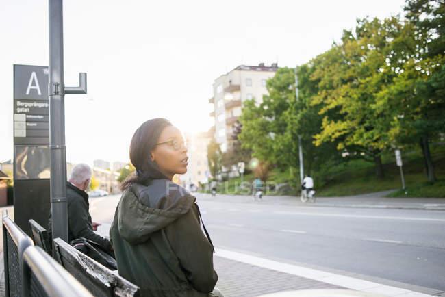 Femme debout à la gare routière et à la recherche. — Photo de stock