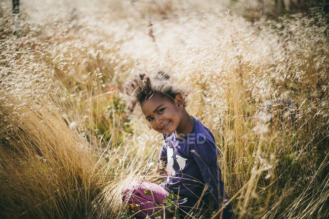 Portrait de jeune fille souriante, assis dans le champ — Photo de stock